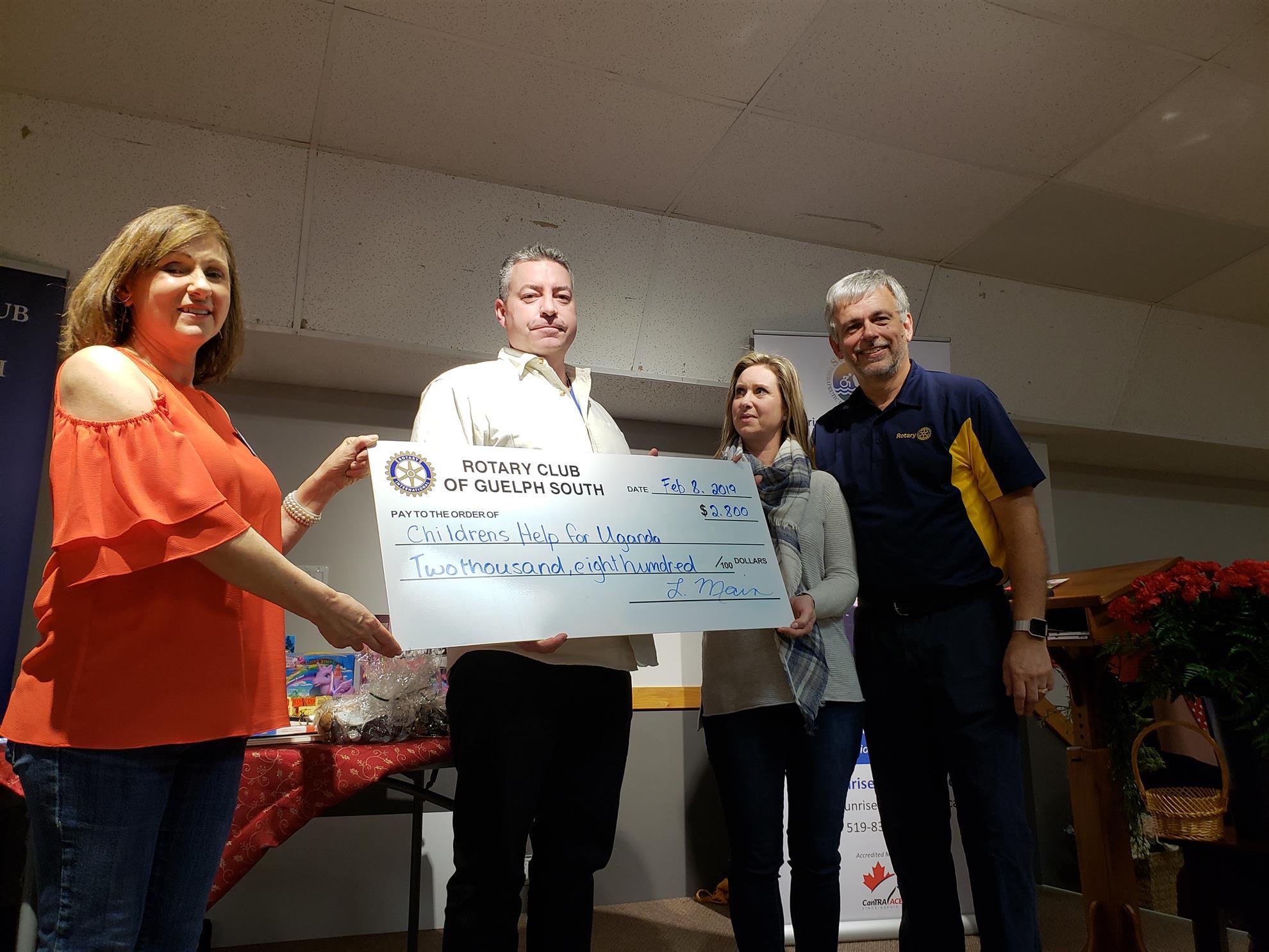 Linda + Brian presenting a $2800 donation to Dennis + Stephanie Devey of Childrens Help for Uganda