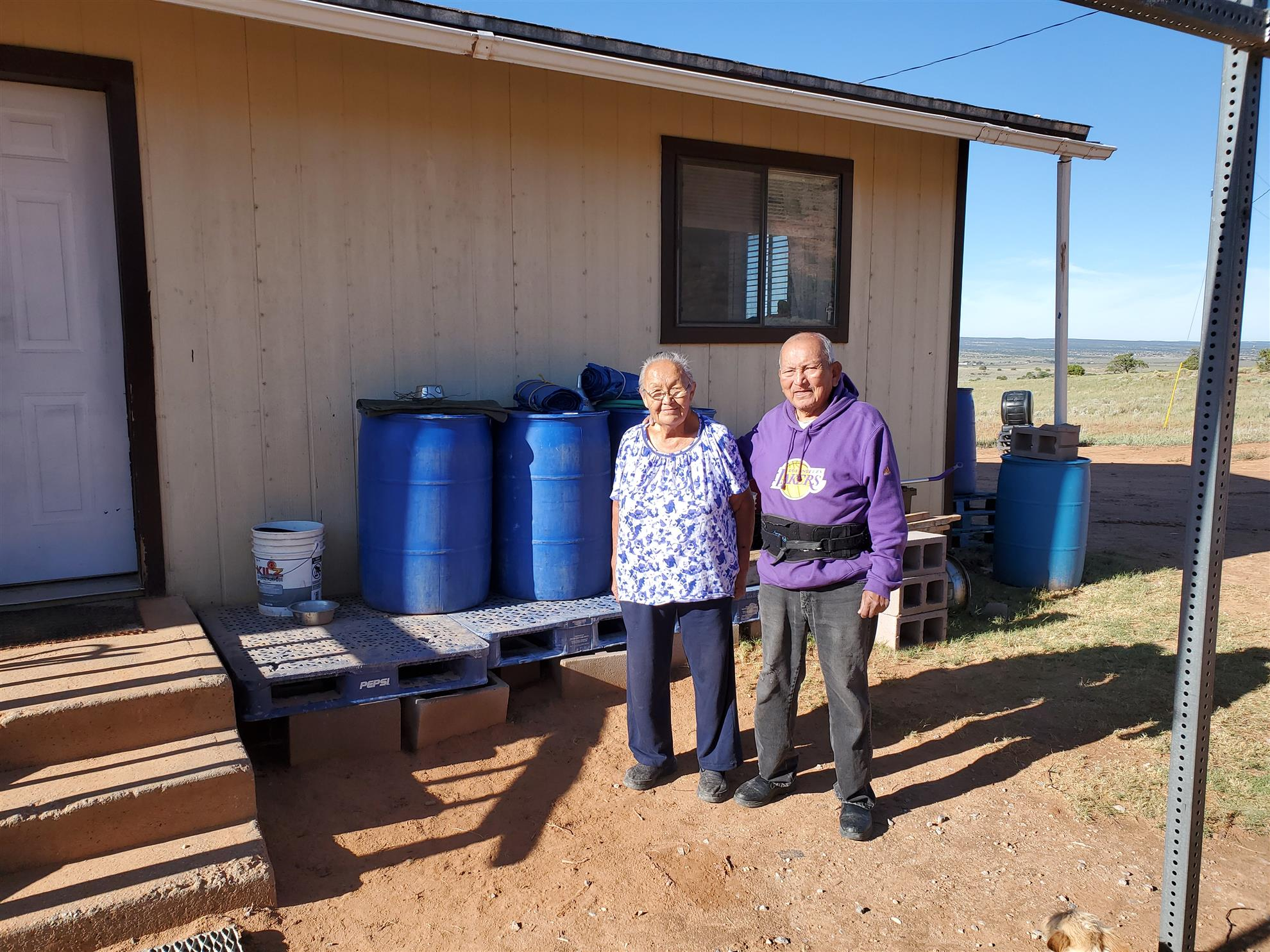 The Jim's: Ida 77 yrs. Joe 84 yrs.  Have lived in home without inside running water and toilet since the early 70's.  Do have electricity. Water stored in three 50-gallon barrels that needs to last one month unless their son brings water hauled in a pick-up truck. After installation: 1,200-gallons and refilled by water truck