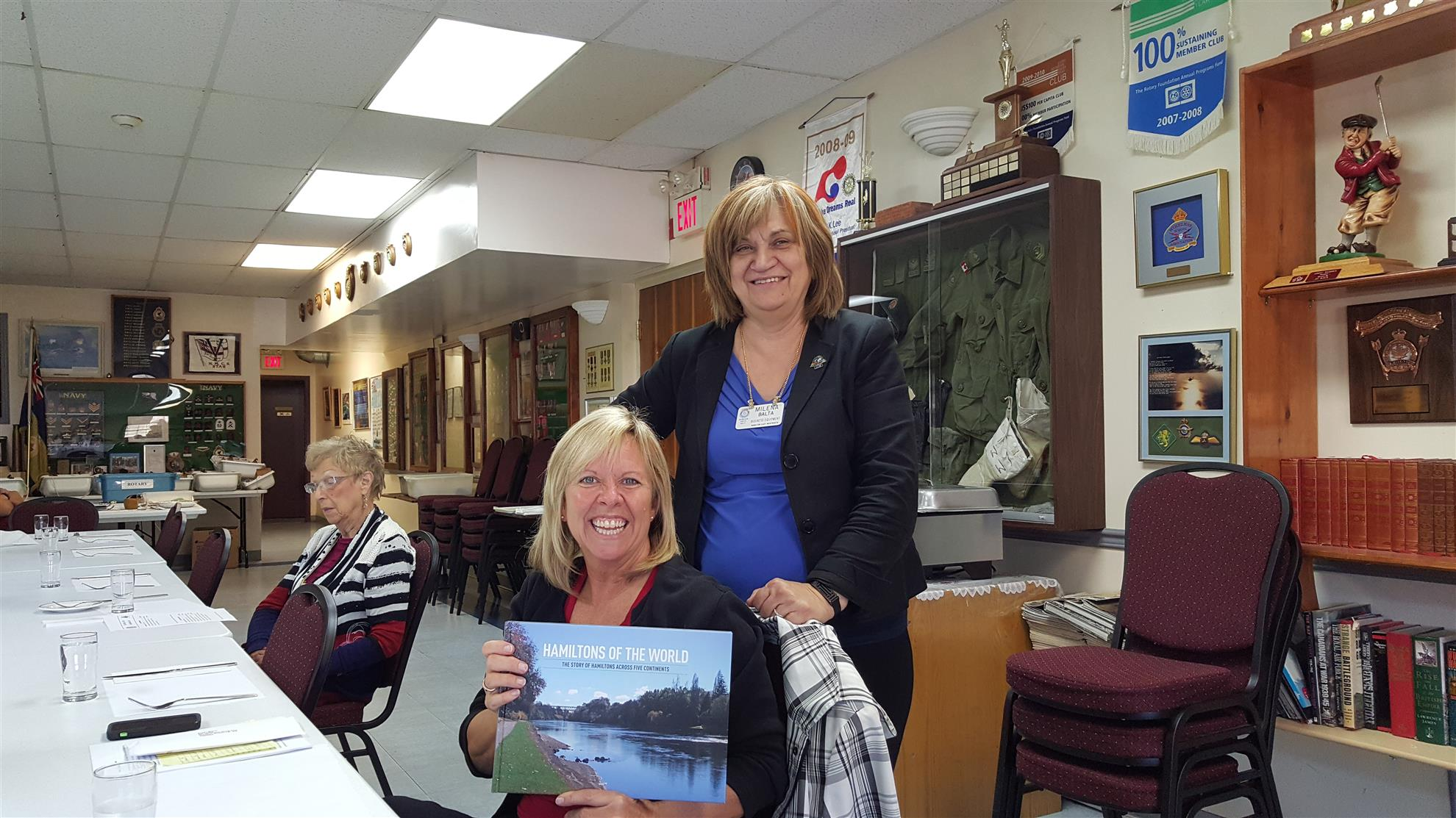 Rotarian Milena Balta presents Susan Morris with a personalized copy of the 'Hamiltons of the World' Rotary Book.