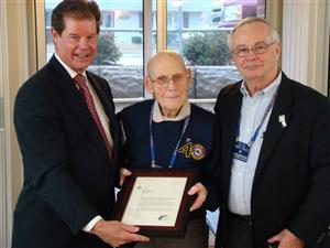in celebration of ernie weeks 100th birthday club president gerry aggus and past district governor bob bruce present a special letter from rotary
