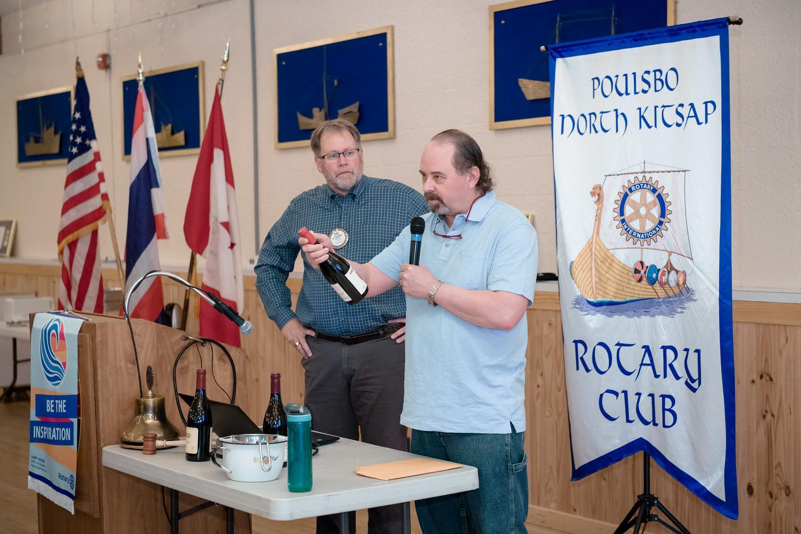Mark Olsen presenting wine for auction