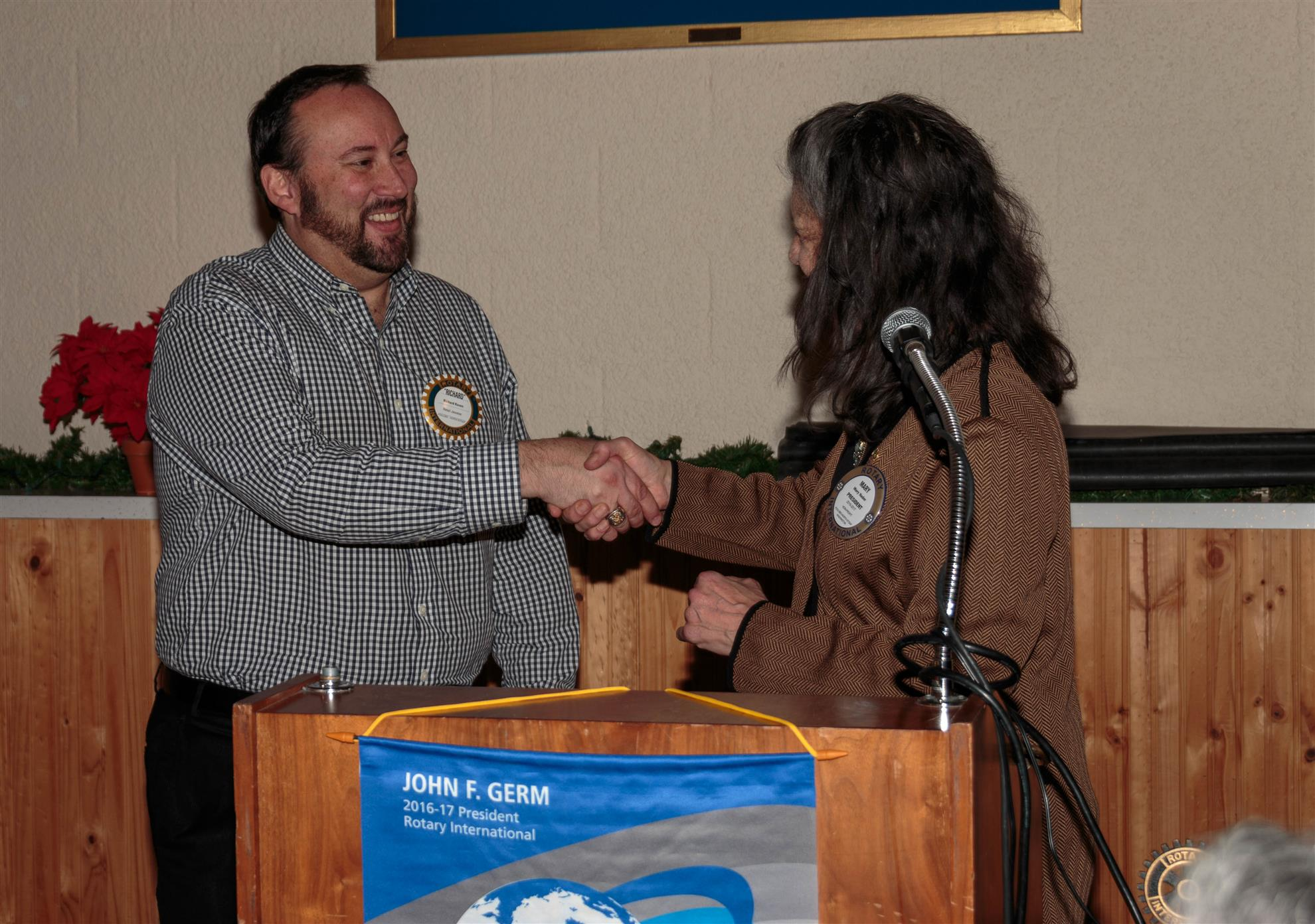 Richard Koven receives congratulations from Club President Mary Nader