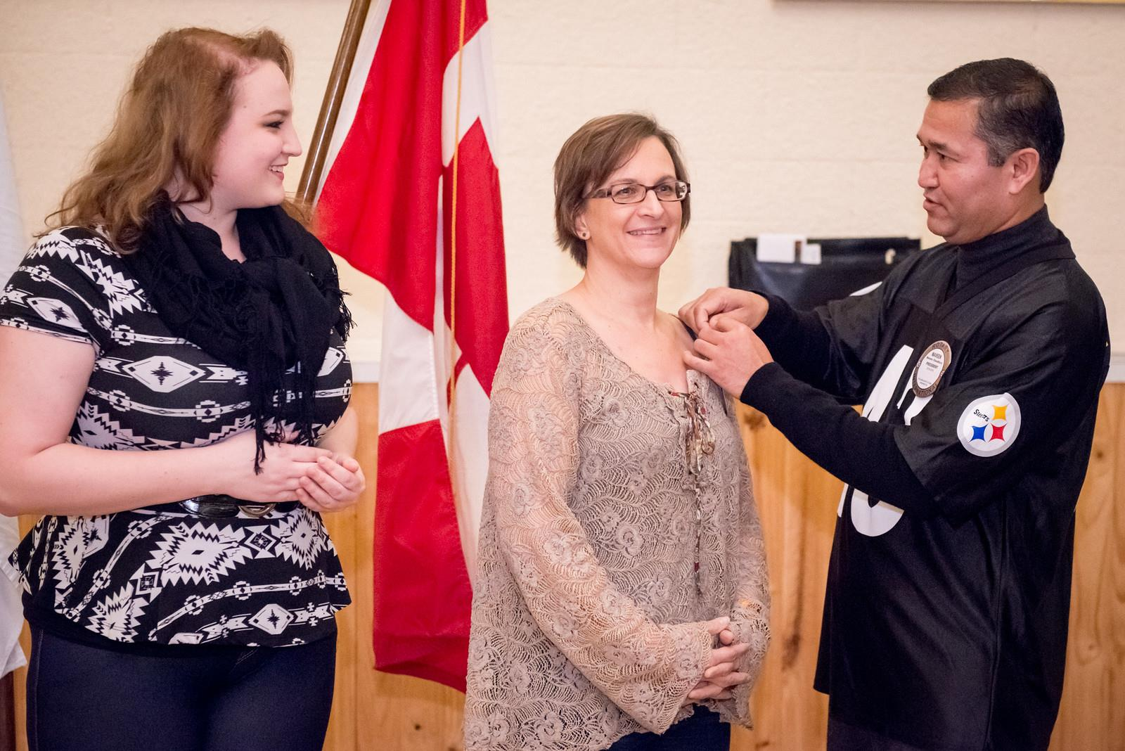 Awardee Aubrey Doyle looks as President Naveen pins a duplicate award pin on her mother Michele