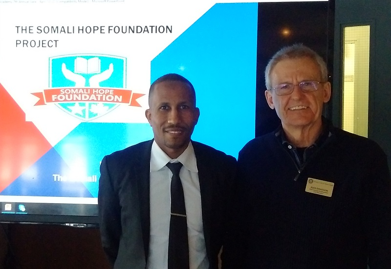 Moe and Alex standing in front of Somali Hope Academy presentation.