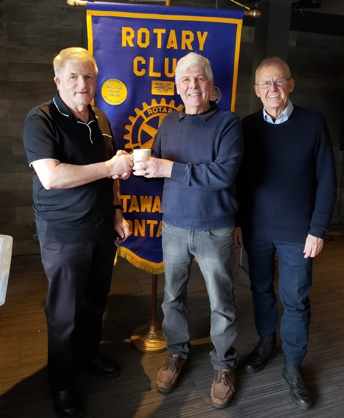Gary Pluim and Alex Davidson from the Rotary Club of Ottawa South flank Master Electrician Earle Clarke.