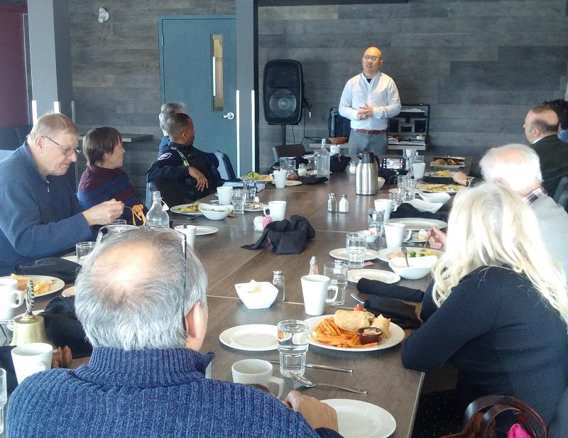 Brandon Fong speaks to several members of the Rotary Club of Ottawa South.