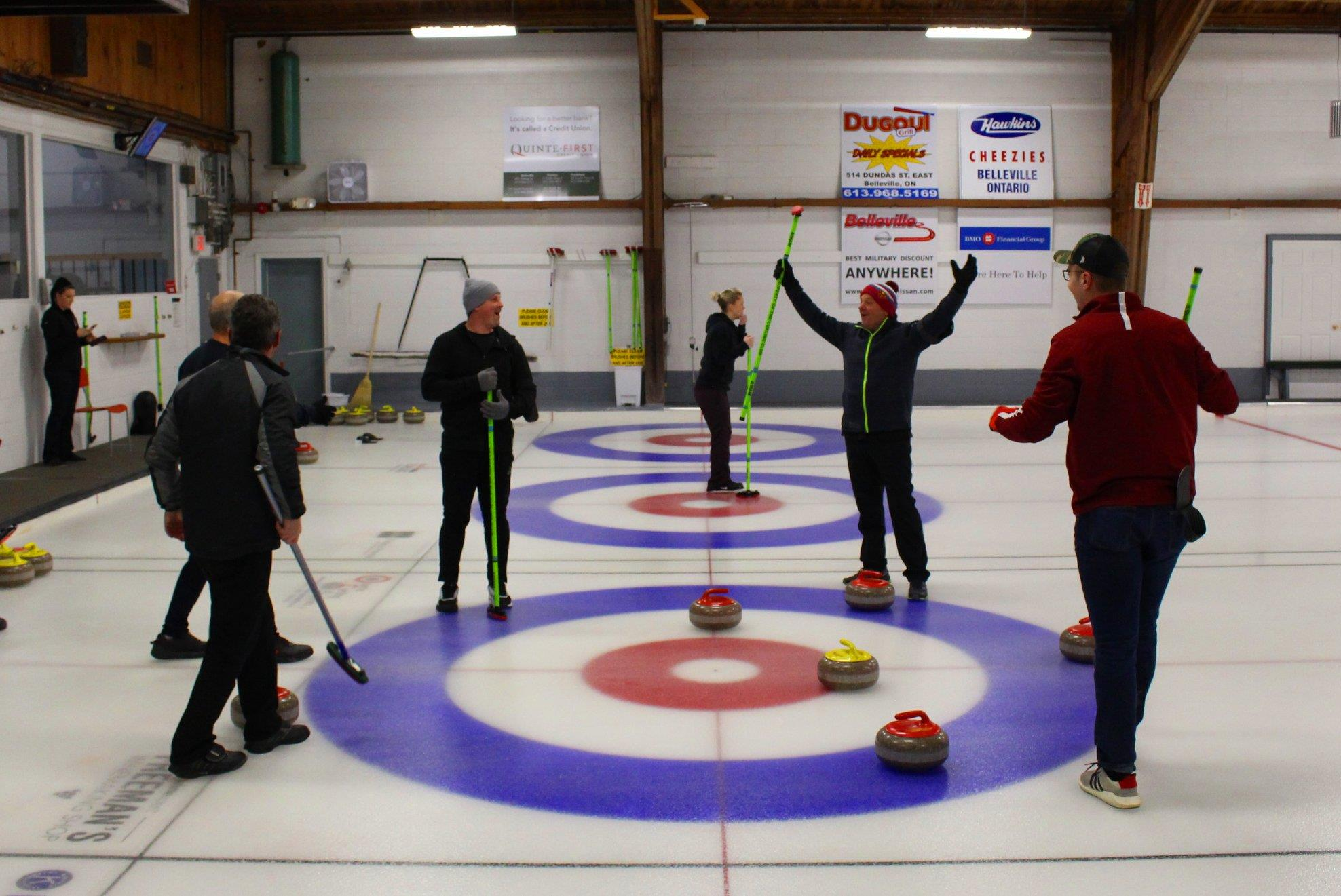 Individuals playing a game of curling
