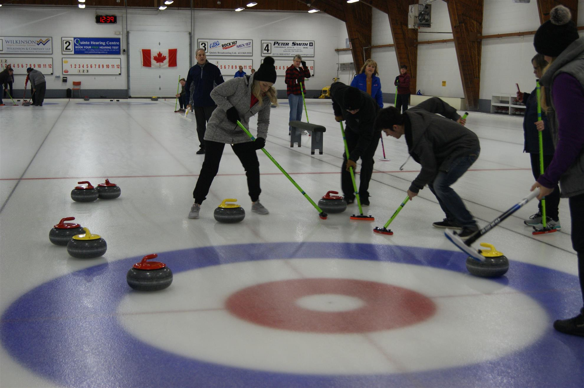 Individuals sweeping a rock at the annual curl for kids