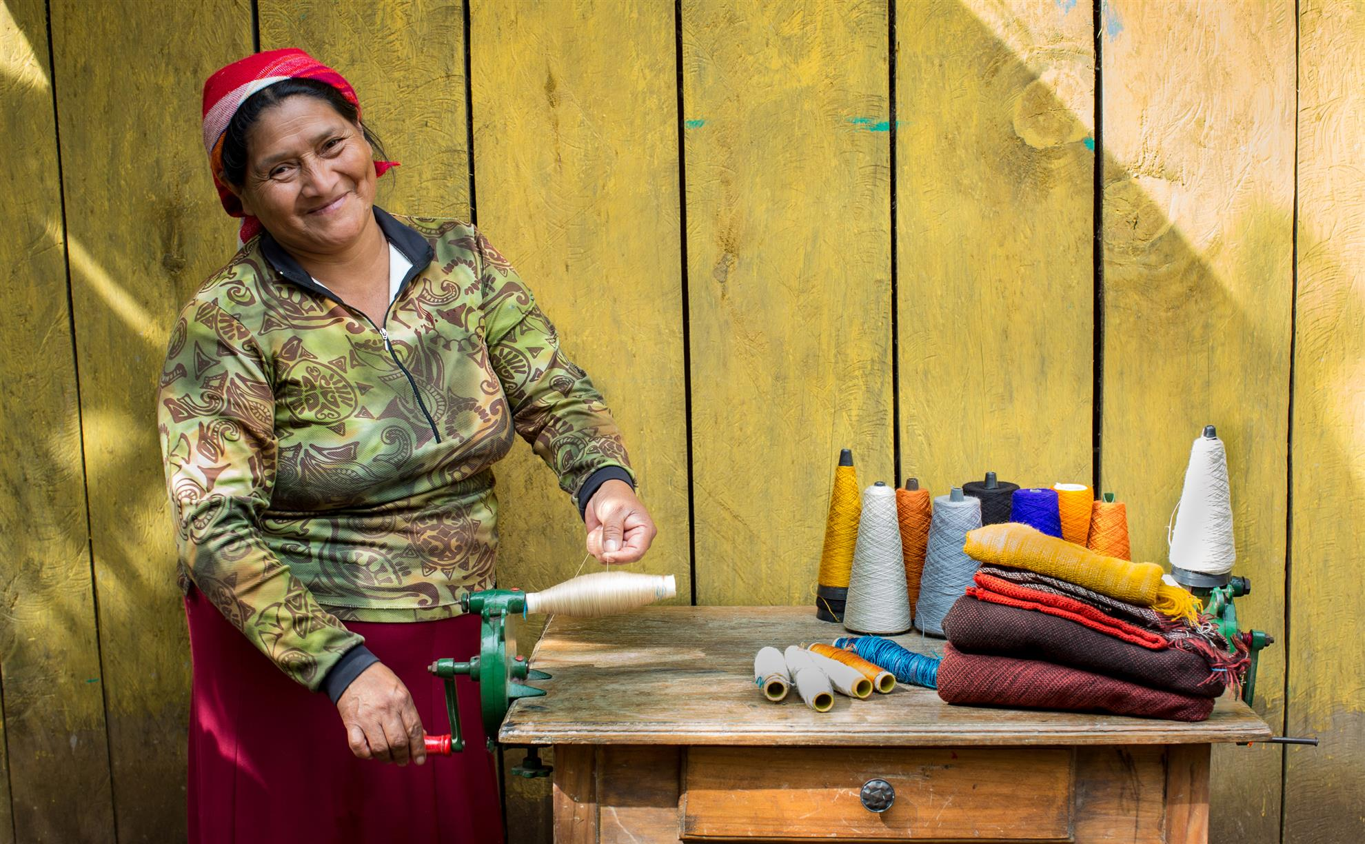 Remigia Dominiguez, a weaver supported by a microcredit loan from Rotarians, spools thread for her loom outside her studio and workshop in El Cacao, Honduras. © Rotary International/Monika Lozinska