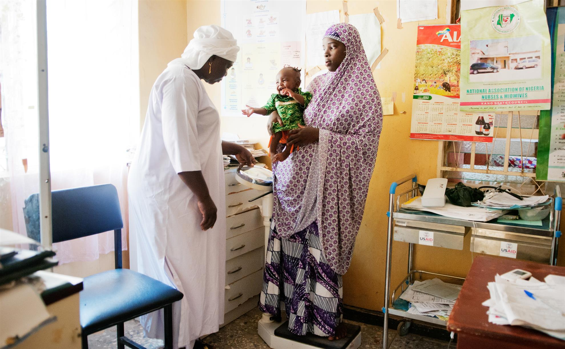 Midwife Tamar Okoh (left) weighs Azima Yahaya and her child Aisha at Sumaila General Hospital in Sumaila, Kano State, Nigeria © Tadej Znidarcic