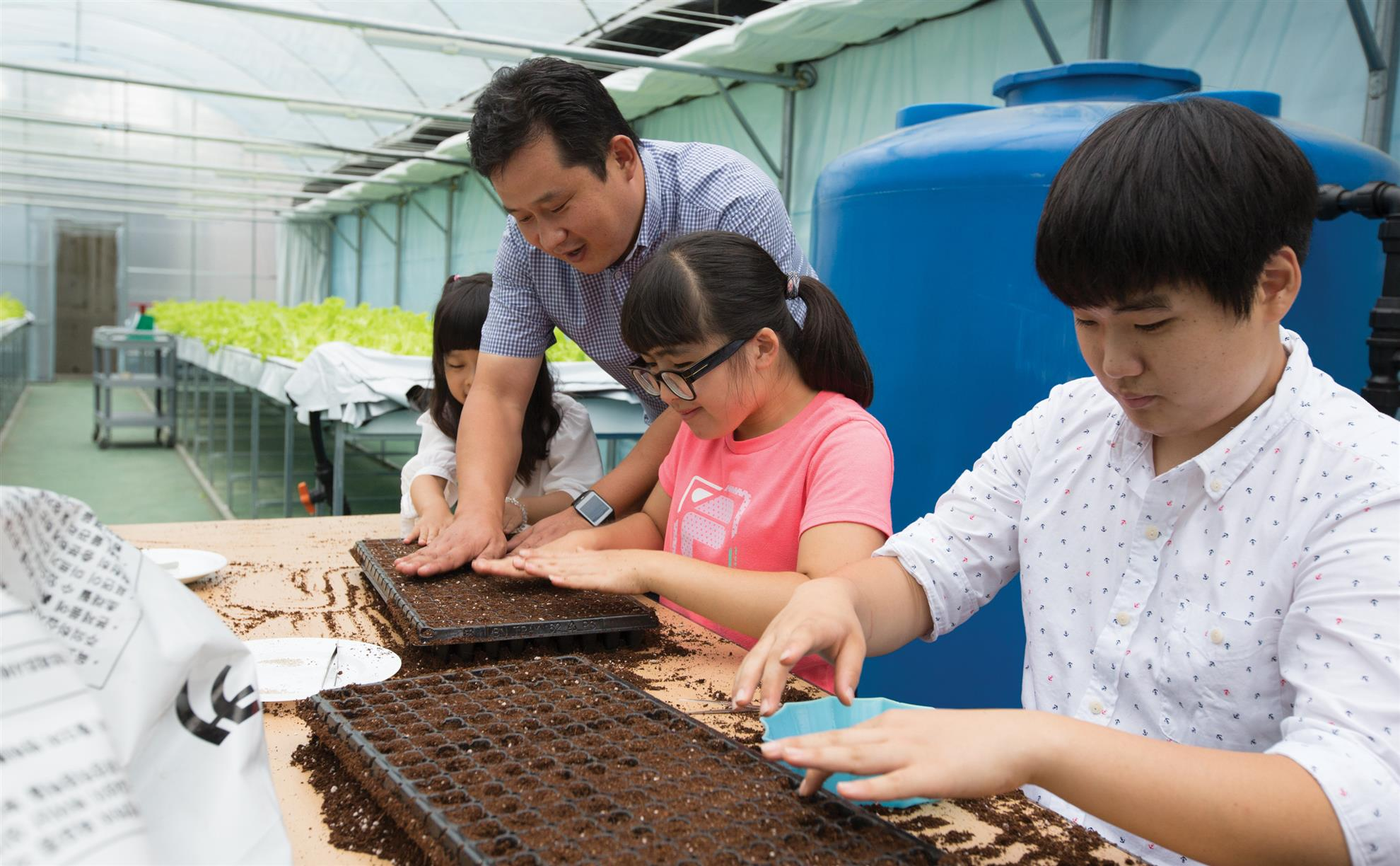 Rotarian mentor Oh Je Kwon shows students Seol Rim Kim and Sun Tak Kwon how to plant seeds in the dirt in the greenhouse © Rotary International