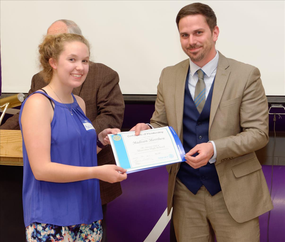 Evan Leary presents Madison Merrihew her Interact Treasurer pin and Certificate of Membership