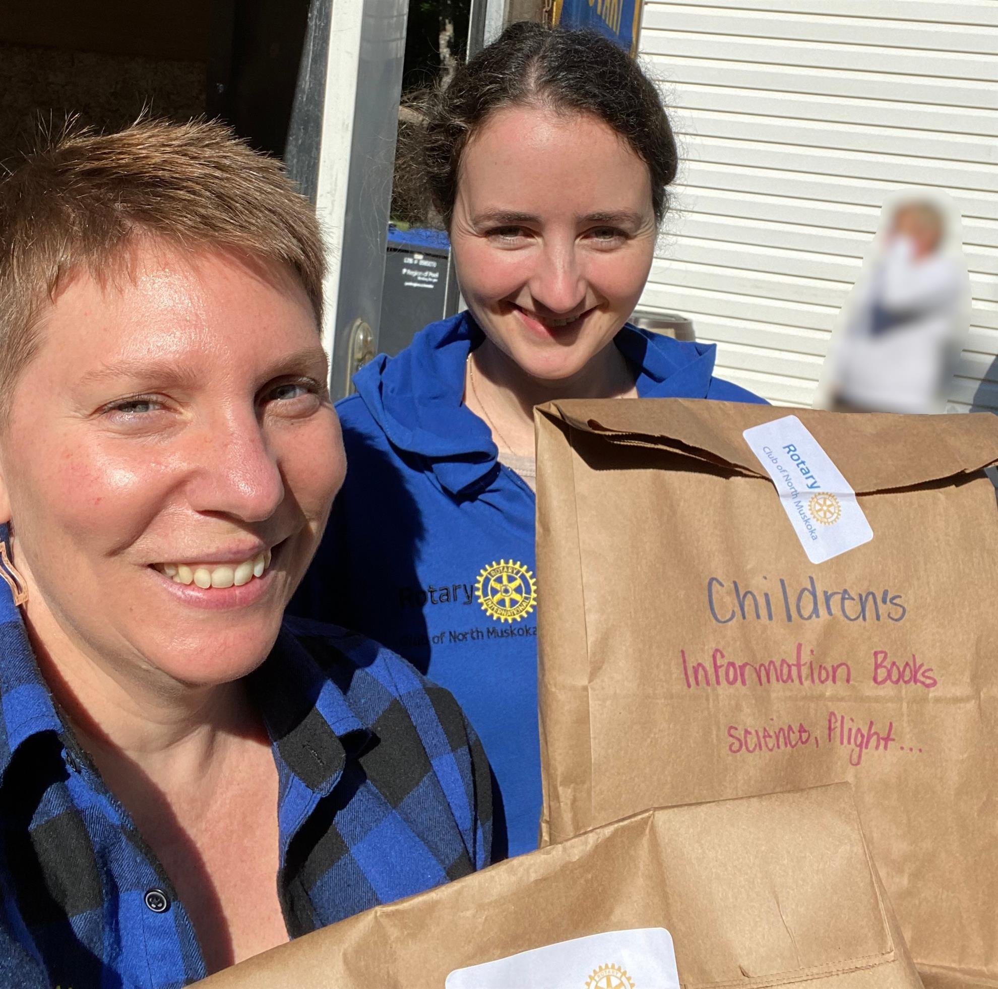 Two women take a close up selfie outside on a sunny day. They hold brown paper bags. One bag reads: Children's Information Books, Science, Flight ...