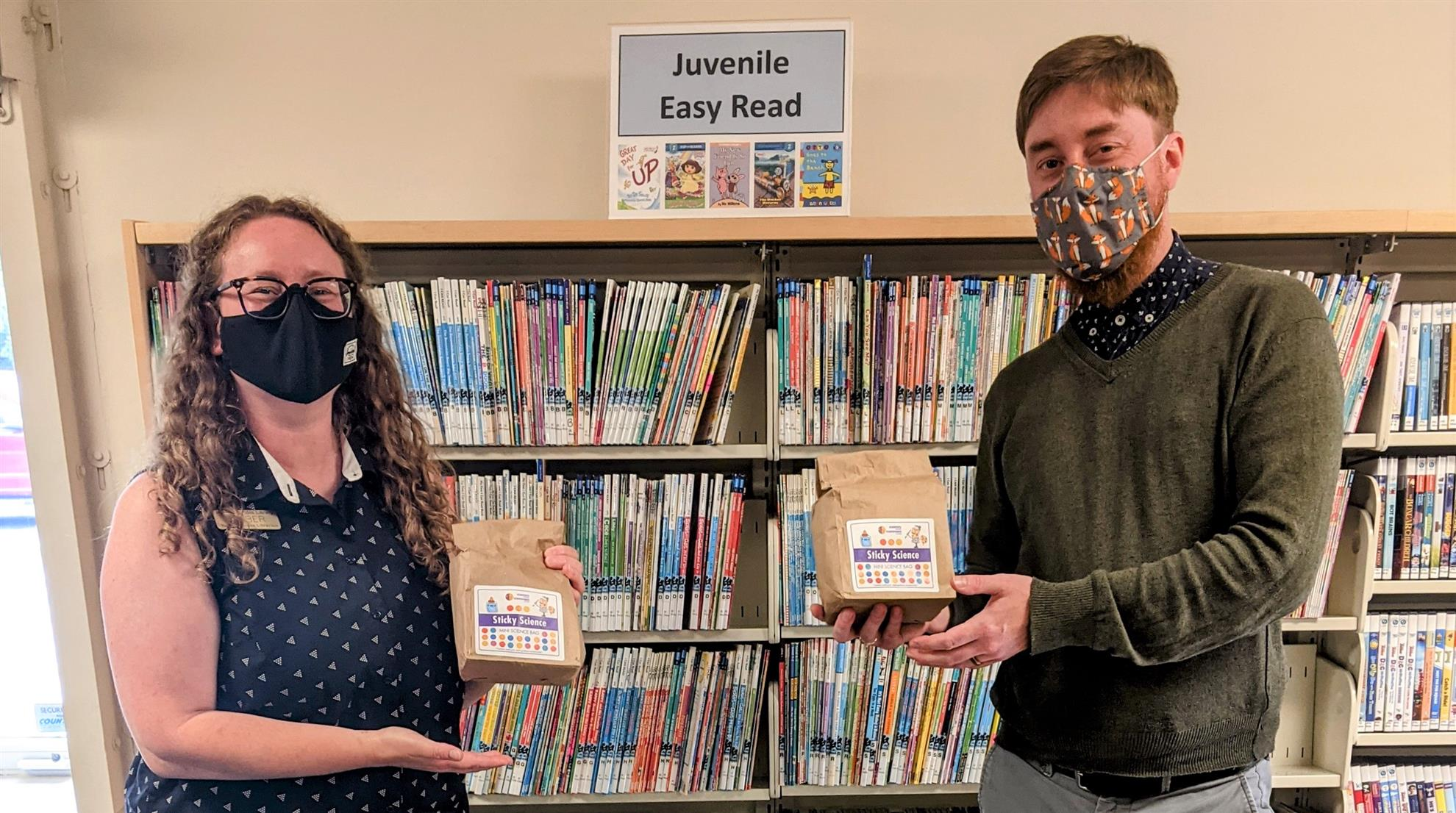 Amber and David in the library with some craft kits that read: Sticky Science