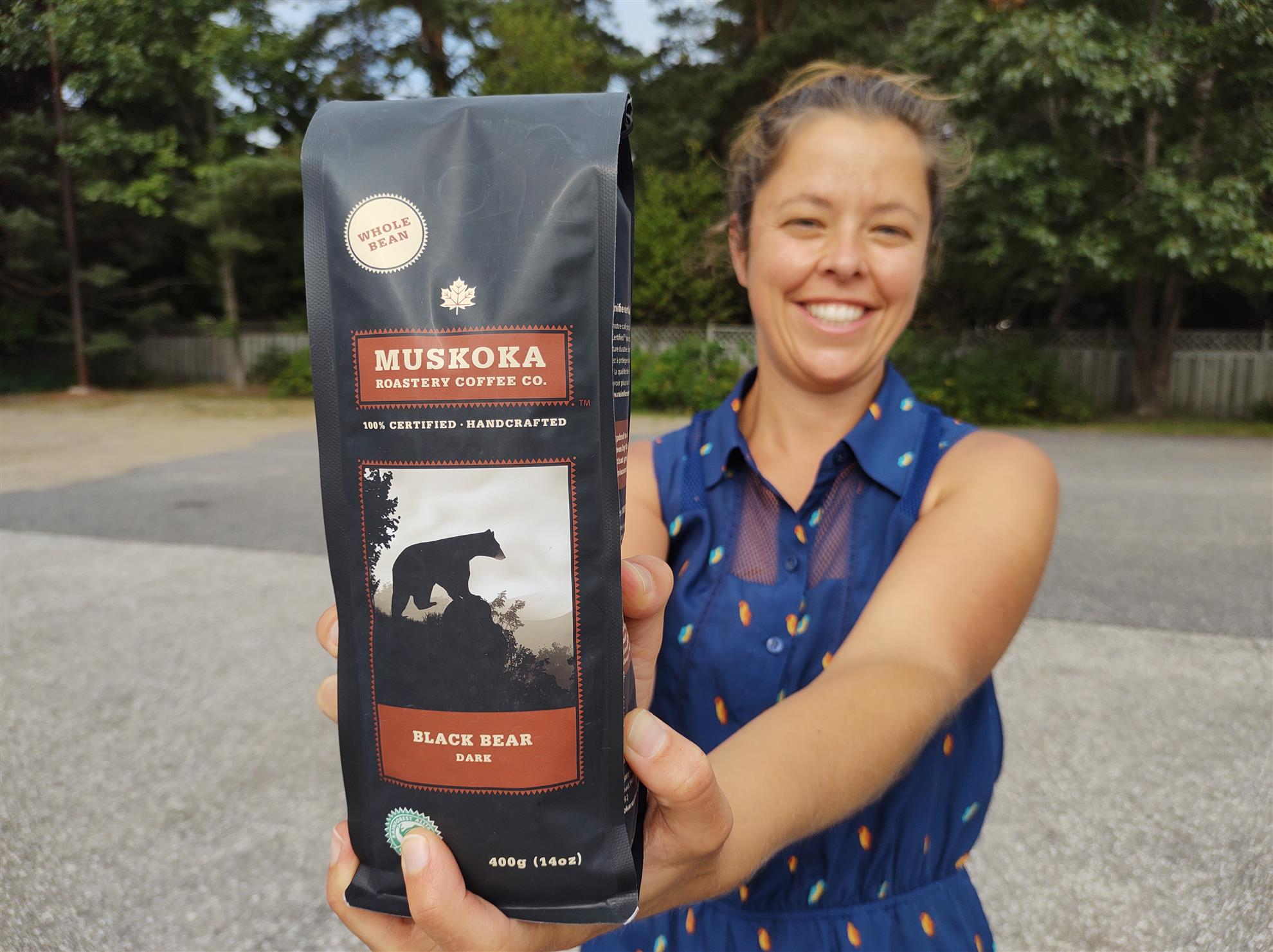 Smiling woman holds 400-gram bag of coffee toward camera. Bag reads: Whole bean Muskoka Roastery Coffee Black Bear Dark.