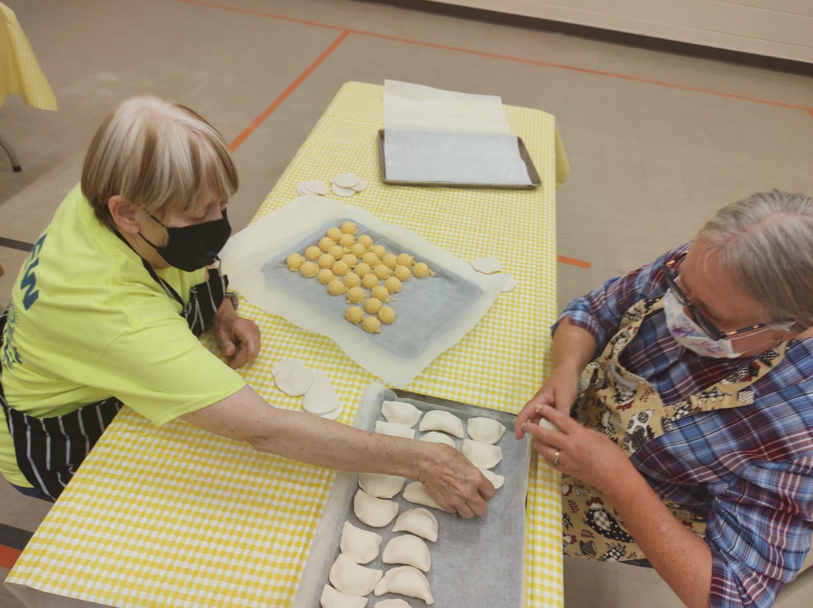 Two women sat at a table and wearing face masks arrange perogies on a baking tray lined with  parchment paper.