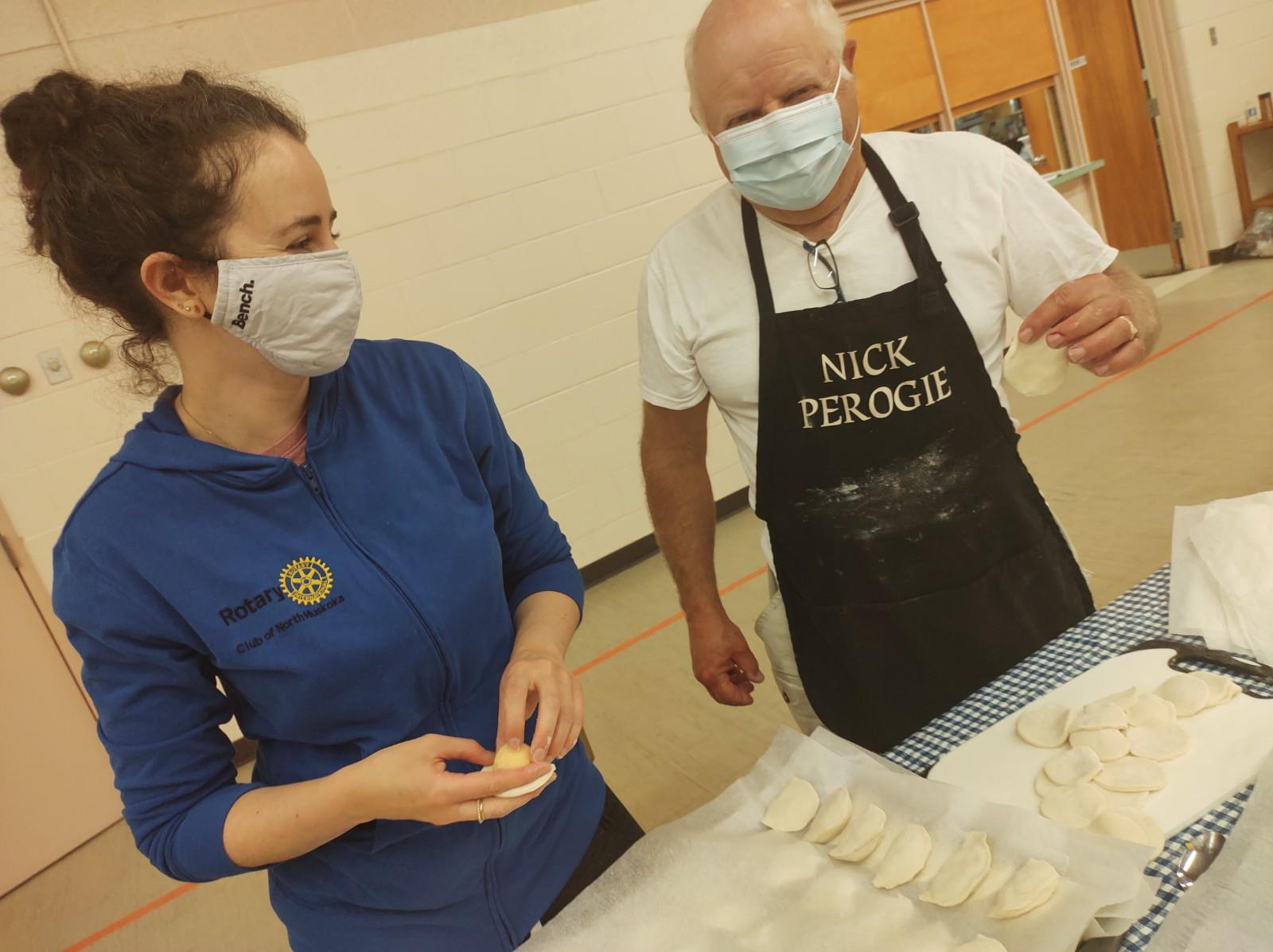 A woman and a man wearing face masks pose for the camera. The woman is wearing a blue shirt with a gold Rotary logo on it. The man is wearing an apron with a bit of flour on it. The apron reads: Nick Perogie.