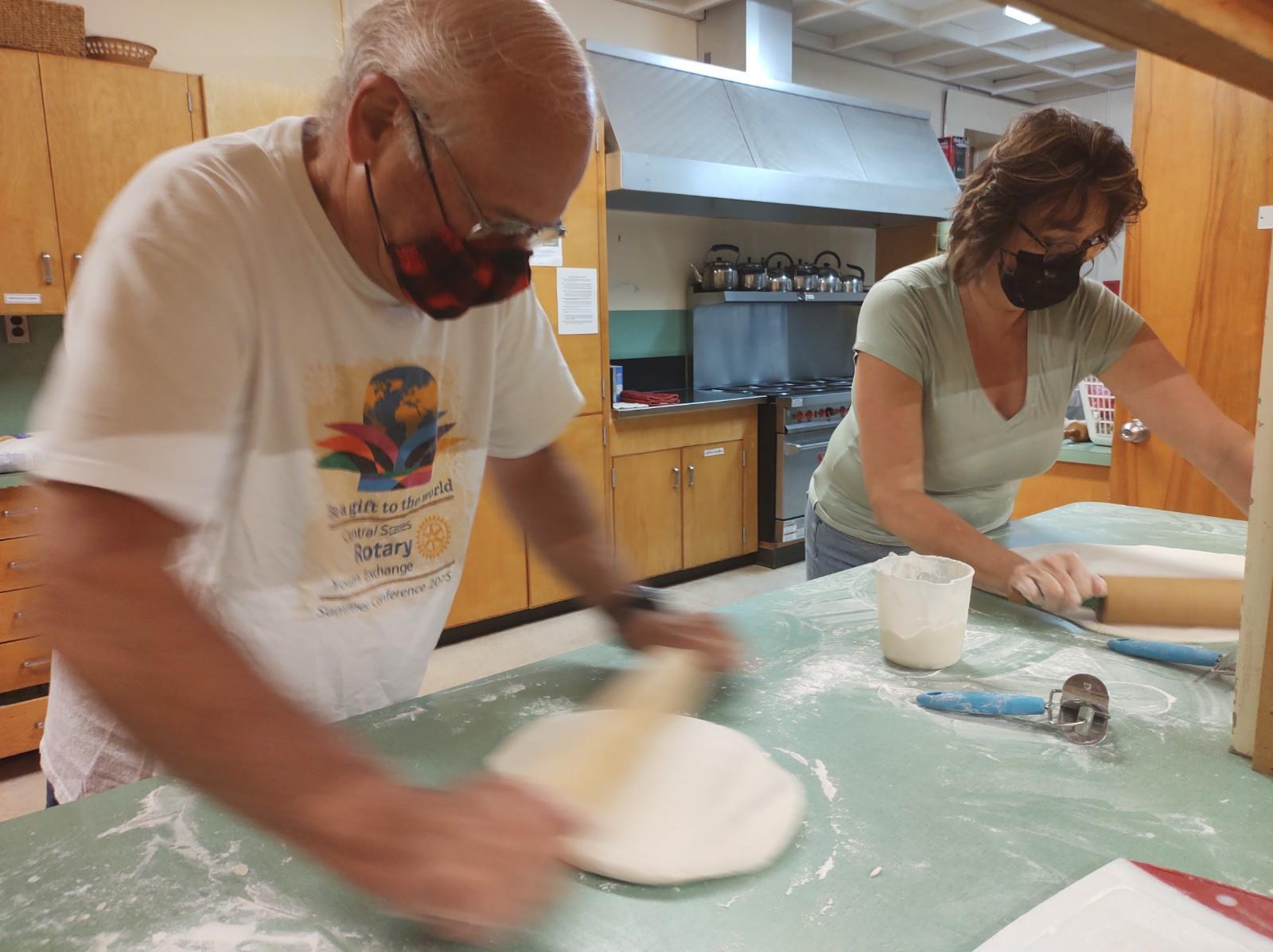 A man and a woman, both wearing face coverings, use rolling pins to roll out dough for perogy shells.