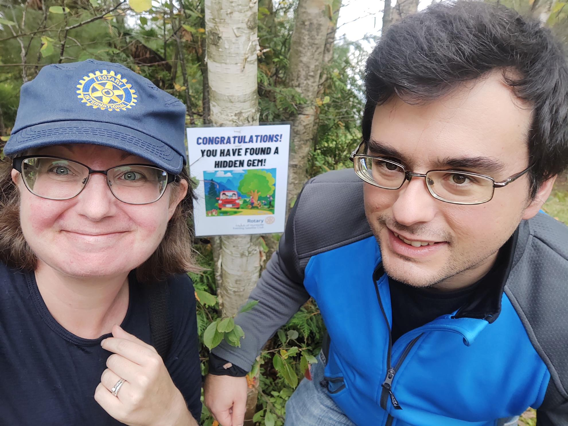 A woman and a man take a selfie outdoors near a poster tacked to a tree. The woman wears a blue ball cap with a gold Rotary International logo on it. Poster reads: Congratulations! You have found a hidden gem.
