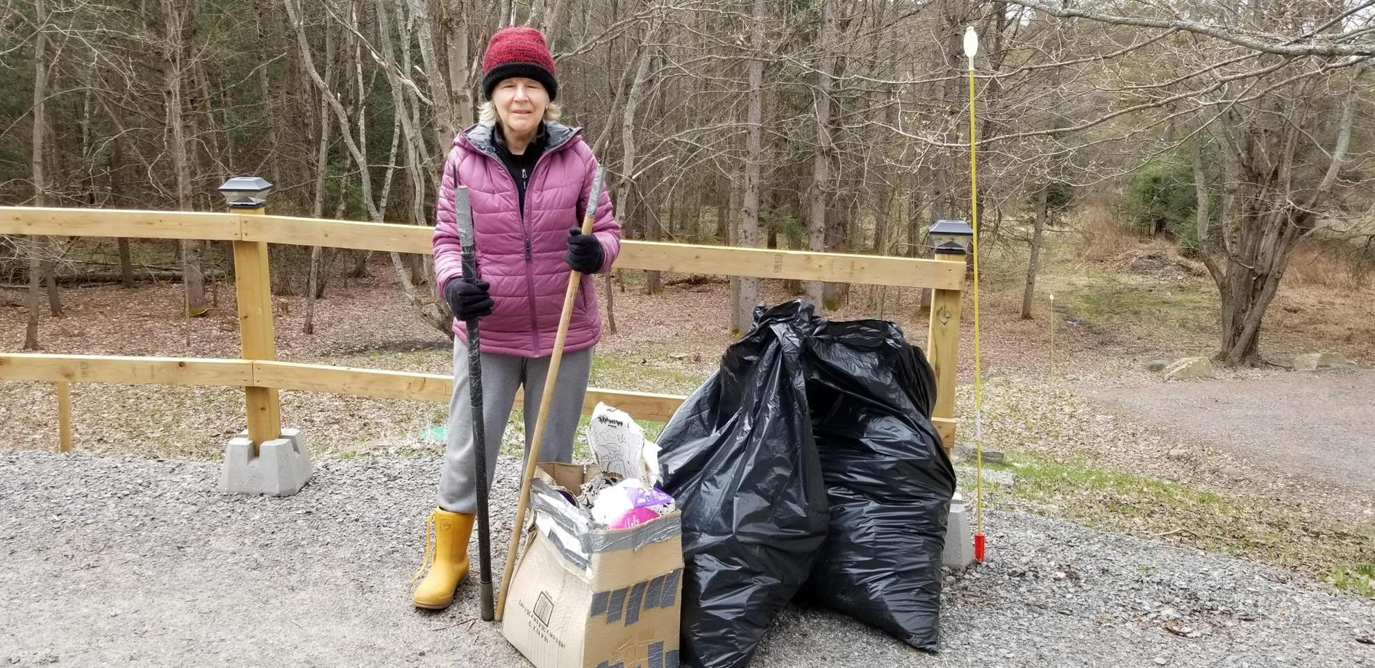 Lynne stands beside a pile of collected trash
