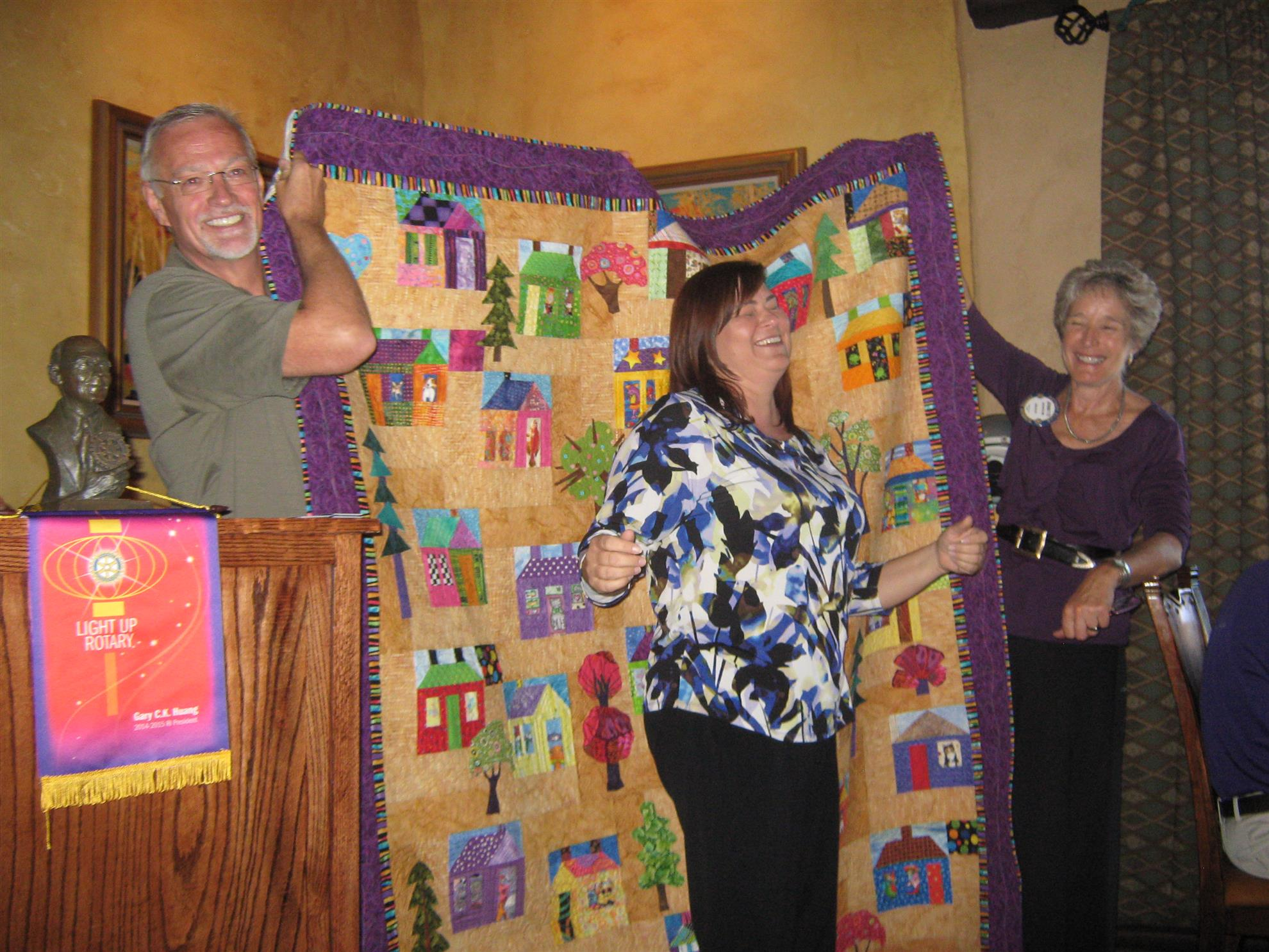 Sandra Gardner does a little victory dance in front of the quilt she has won.