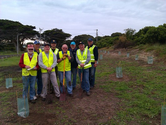 Rotary Club members pose for a photo after completing their tree planting