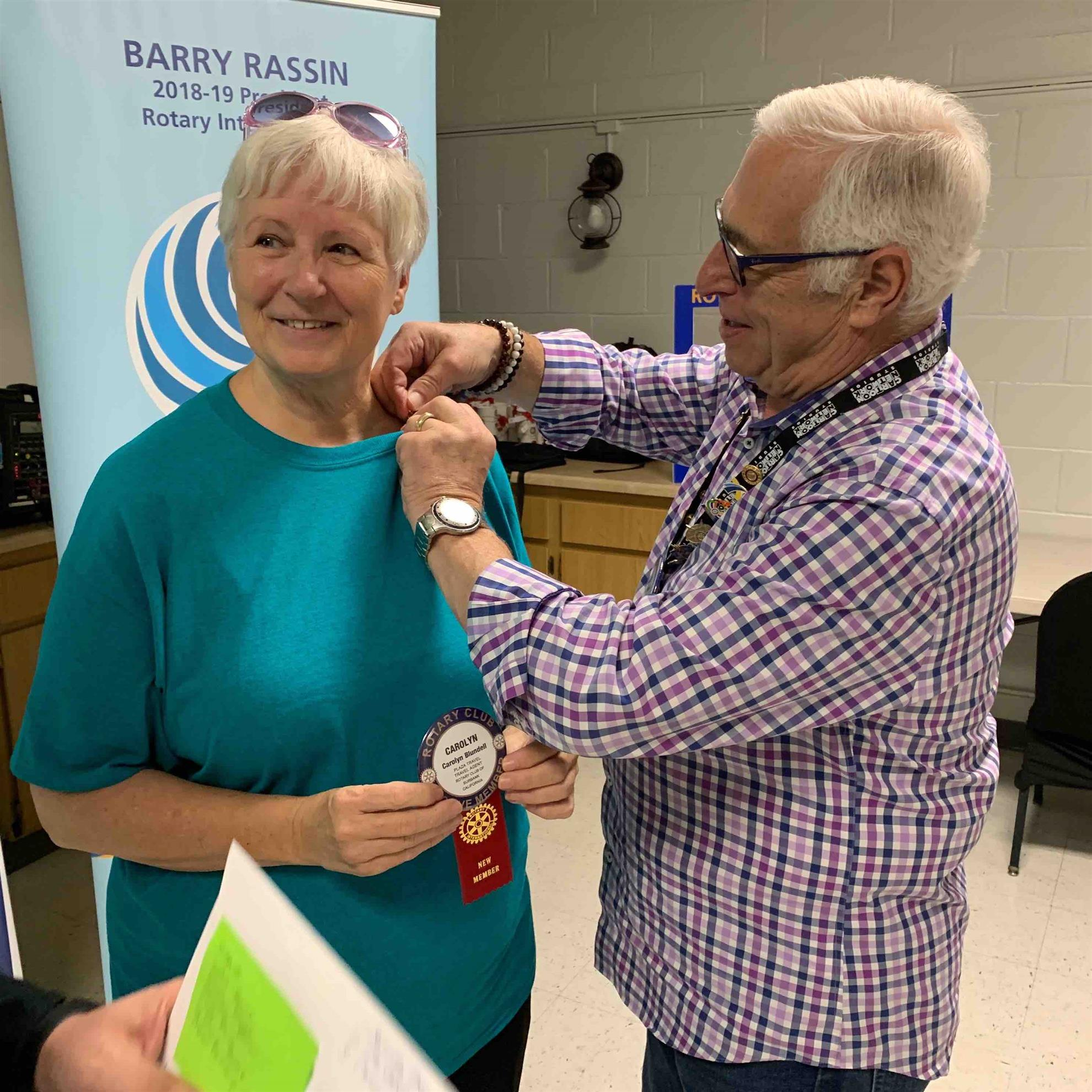 Carolyn Blundell receiving her Rotary Club pin from her Sponsor: Barry Gussow