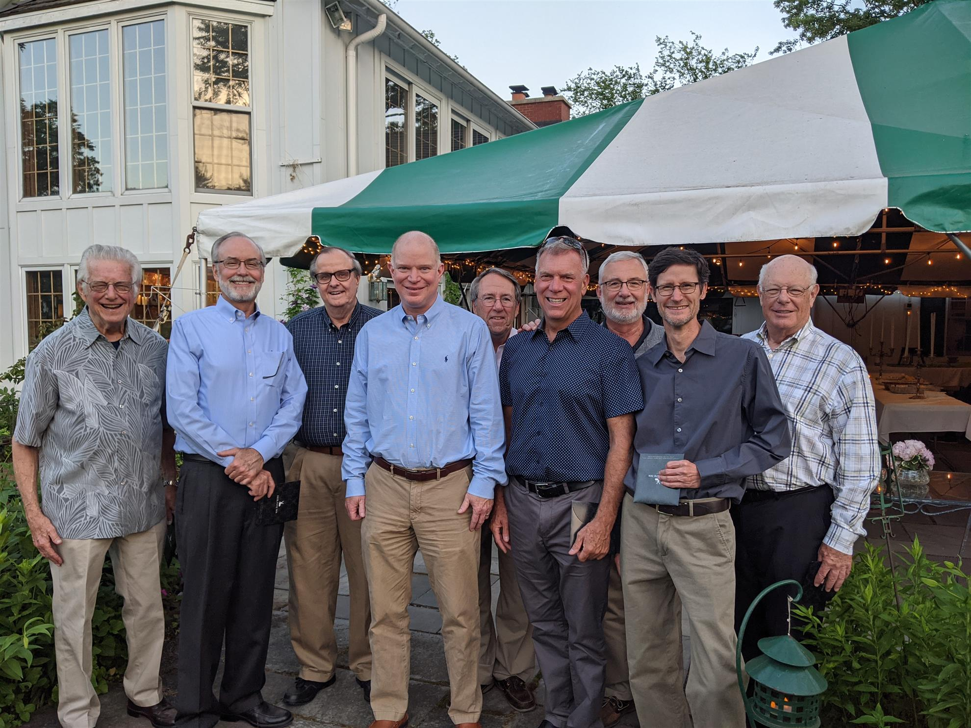 Dick, Jerry, Larry, John H, JJ, John B, Mark, Steve, and Tom stand in front of a white and Lake Forest green party tent.