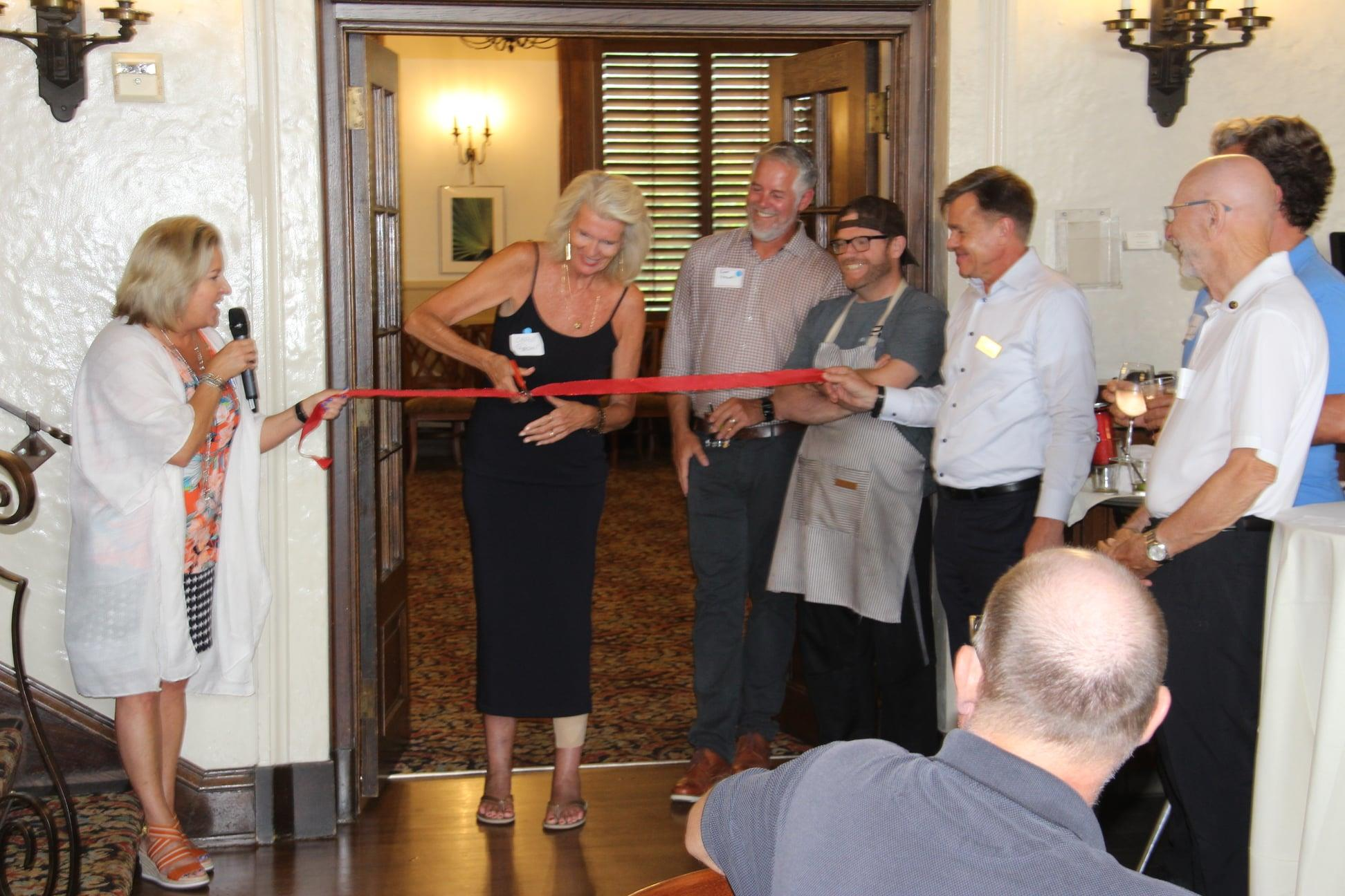 Carol Russell performs the ribbon-cutting, officially inaugurating City of Lakes at the Woman's Club of Minneapolis