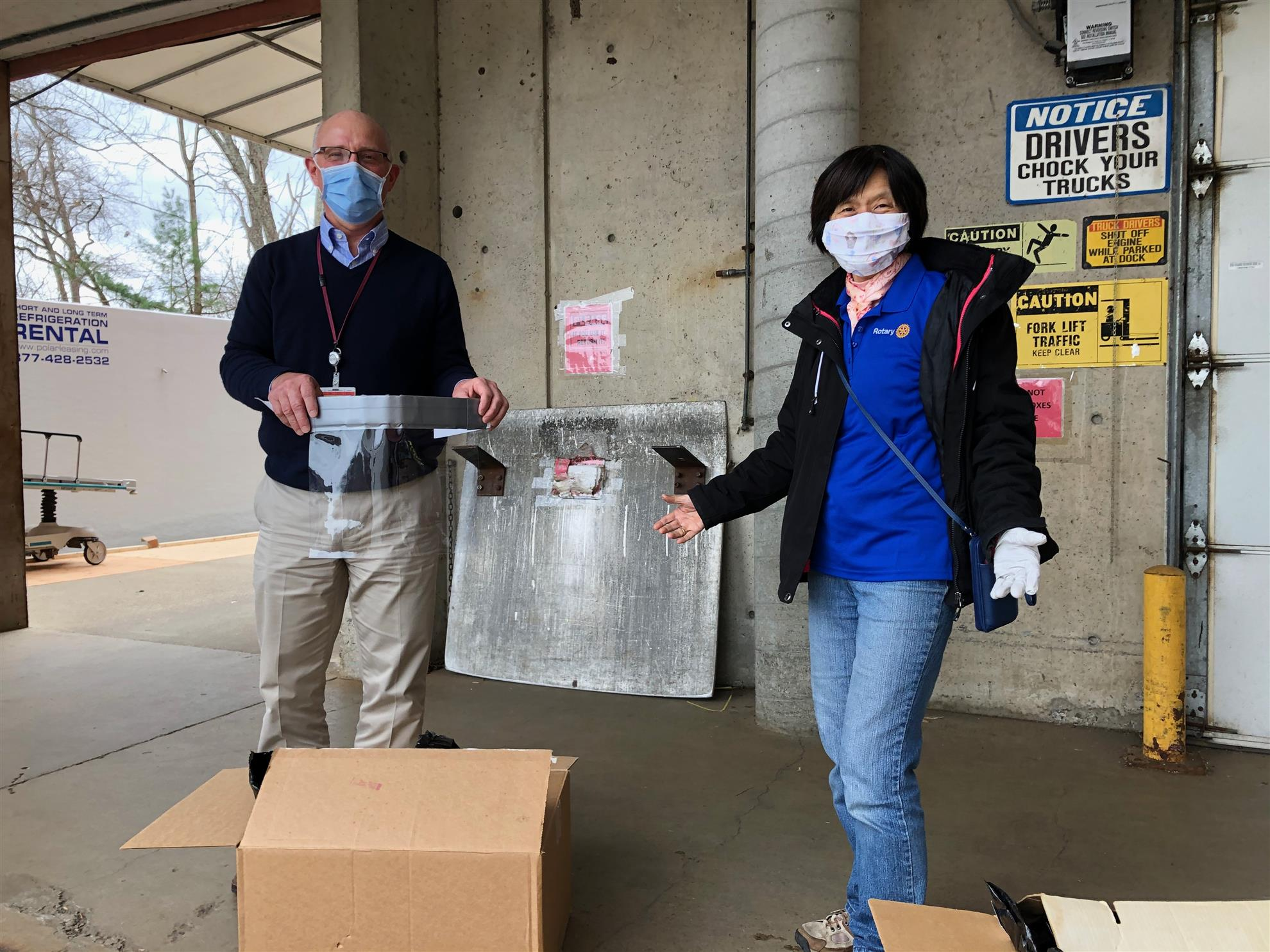 Rotarian Sze-Wen Kuo (President-Elect of Bedford RC) presents 100 face shields to Karl Kussin, VP Emerson Hospital.