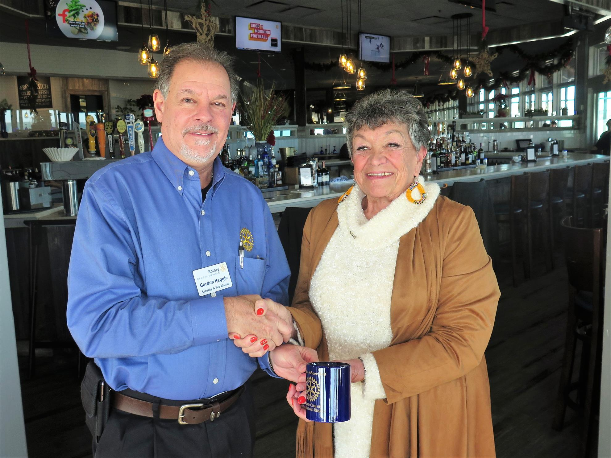 Rotary Club of Greater Long Branch President-elect Gordon Heggie presents guest speaker Sylvia Allen with gift.