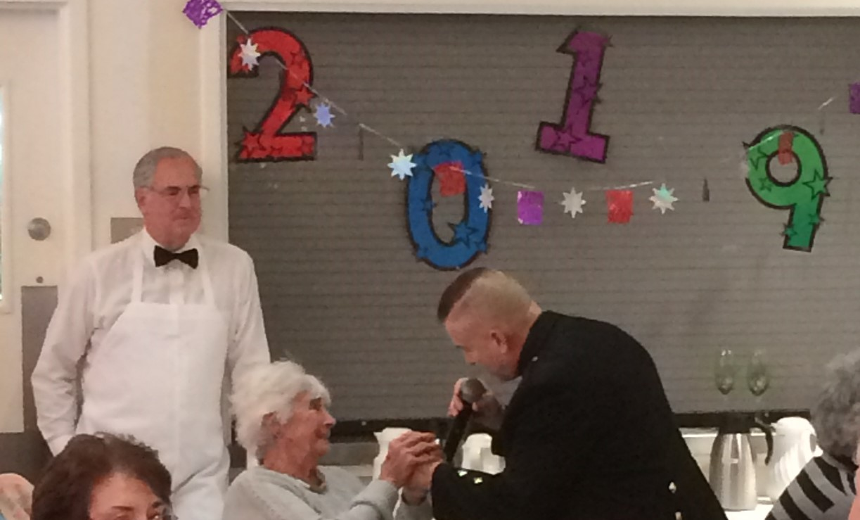 """The Duxbury Rotary Club helped to sponsor a luncheon complete with """"bubbly"""" and entertainment featuring Dan Clark, the Singing Trooper and his wife, Mary, to serenade Duxbury Seniors for a New Years Eve at Noon Party on 12/31/2018. The music was a huge hit as Dan and Mary saluted each of the nations services and did traditional holiday songs.  Each year the Duxbury Rotary Club dons their best waitstaff outfits and serves the Seniors in our community, giving them cheery smiles, a few jokes, and helping them to enjoy the present moment though they may be mourning the loss of dear ones.  It is a blessing for us to serve them."""