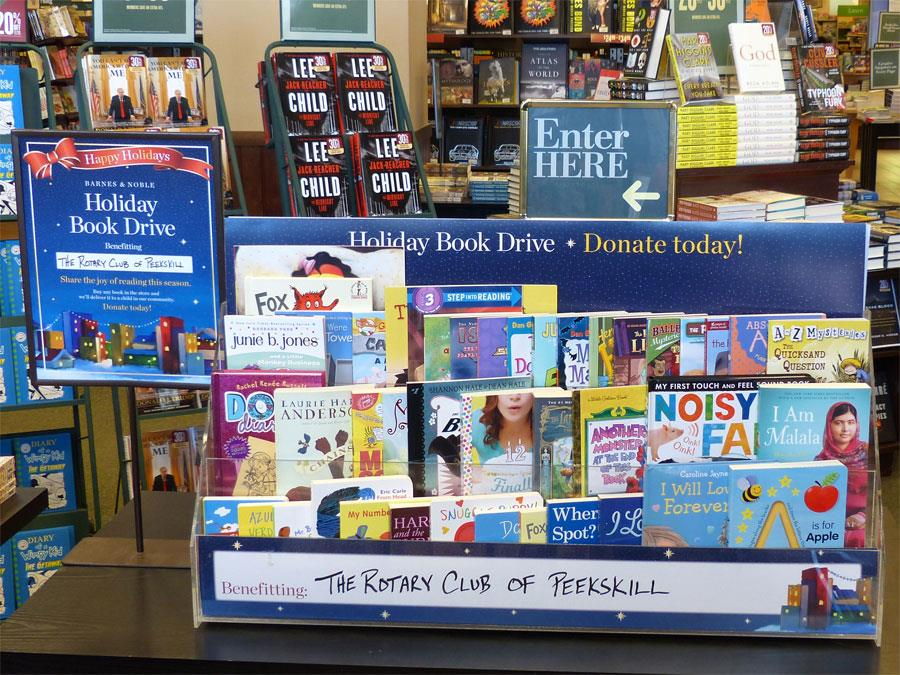 Barnes & Noble Holiday Book Drive display table with books piled high.