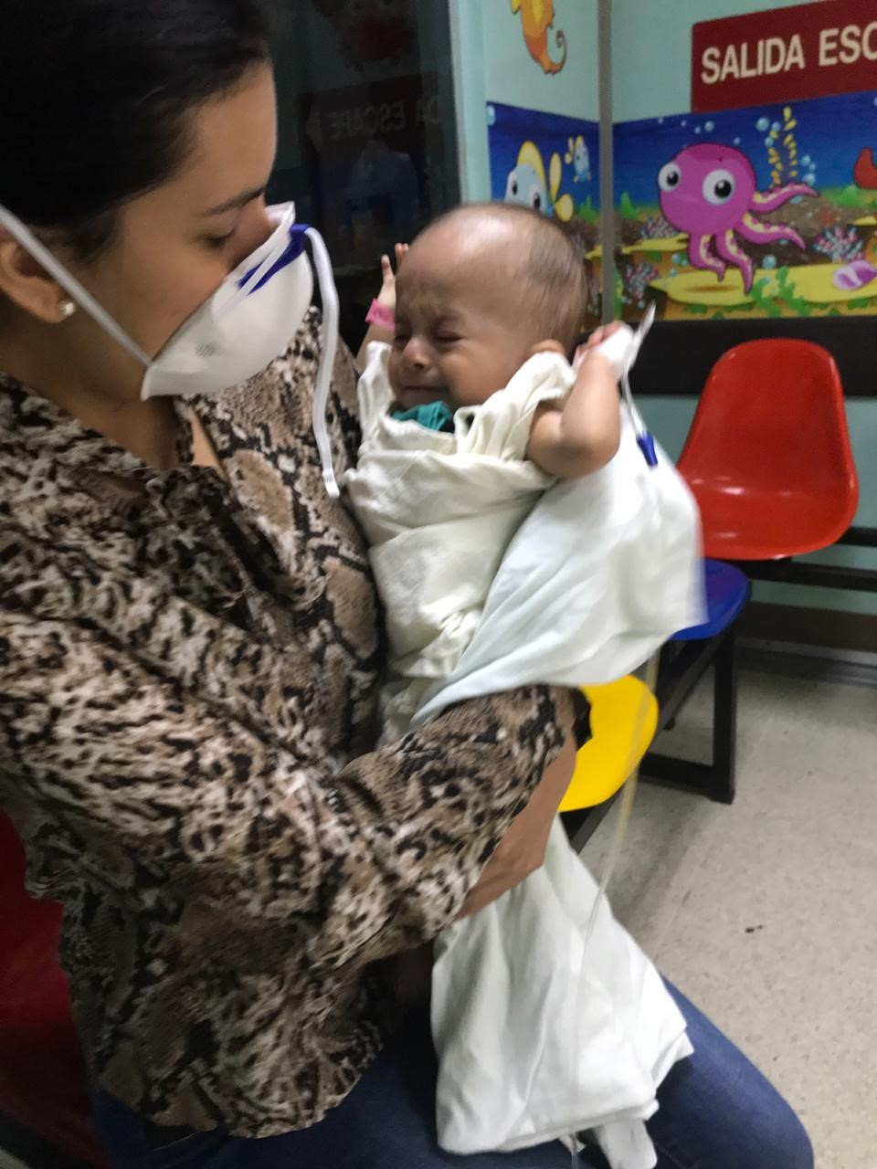 Mother wearing surgical mask holding infant.