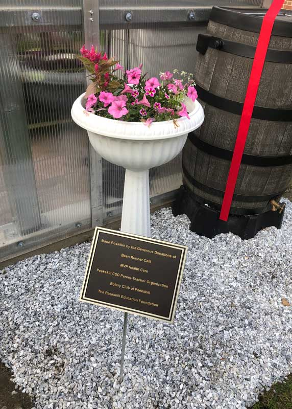 Flower pot and plaque in front of the greenhouse.