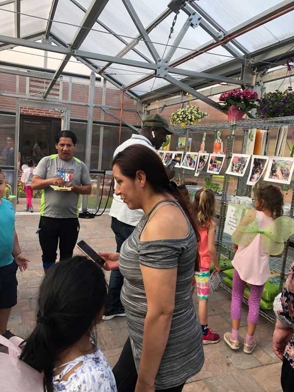 Woodside Elementary School greenhouse interior with kids and adults inside. Poster hang on one wall.