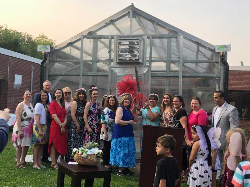 Woodside Elementary School greenhouse with group of people in front cutting ribbon.