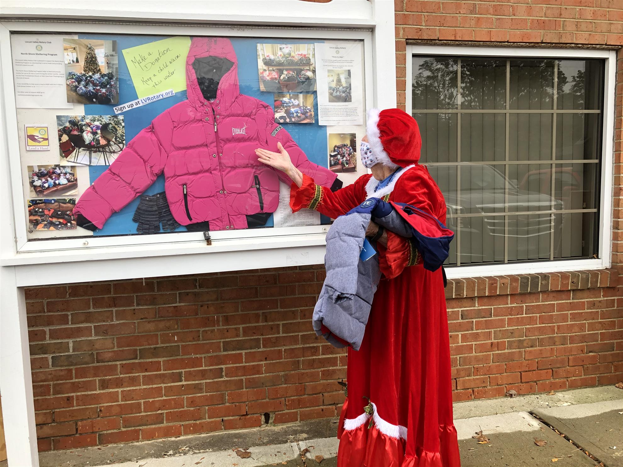 Mrs. Claus looks at the Girl's Coat in the Rotary Information Kiosk