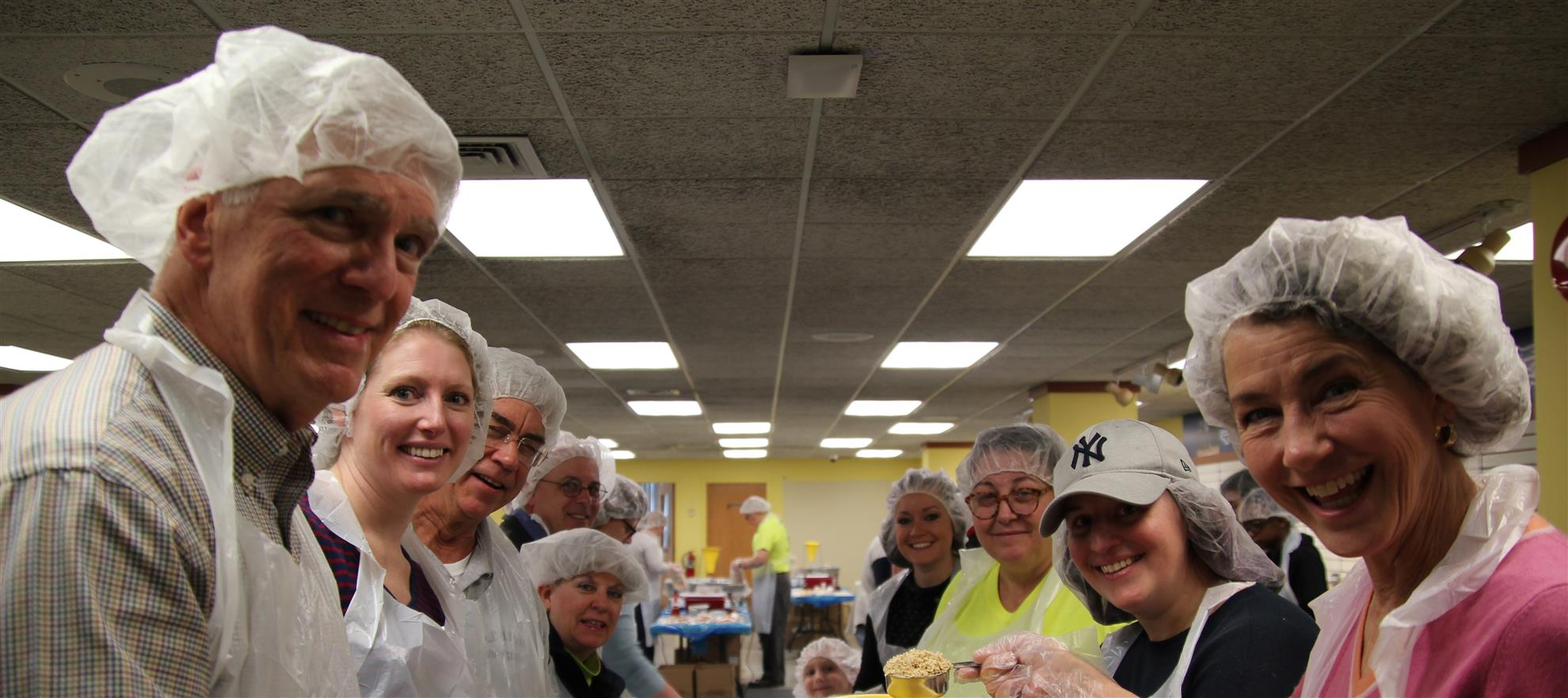 WE JOIN AREA CLUBS TO PACKAGE MEALS FOR COMMUNITY FOOD PANTRIES