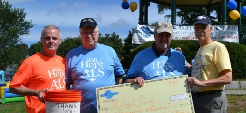 Wilmington Rotarians Harry Cunningham (second from left) and Mike Burns (second from right) present the Angel Fund with a check.