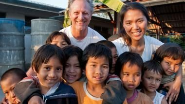 David Stevenson and Asa Jupoa Stevenson co-founders of the Akha Training Center in Mae Suai, Thailand with some of the Akha children they have helped.