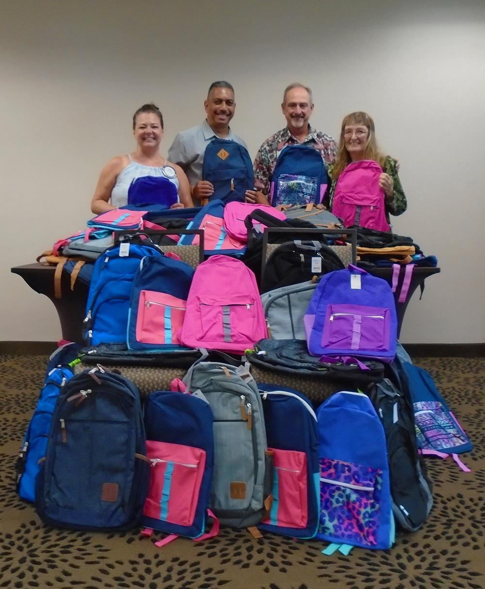 Officer Van Reyes of the Hawaii County Police Dept. accepting the backpacks