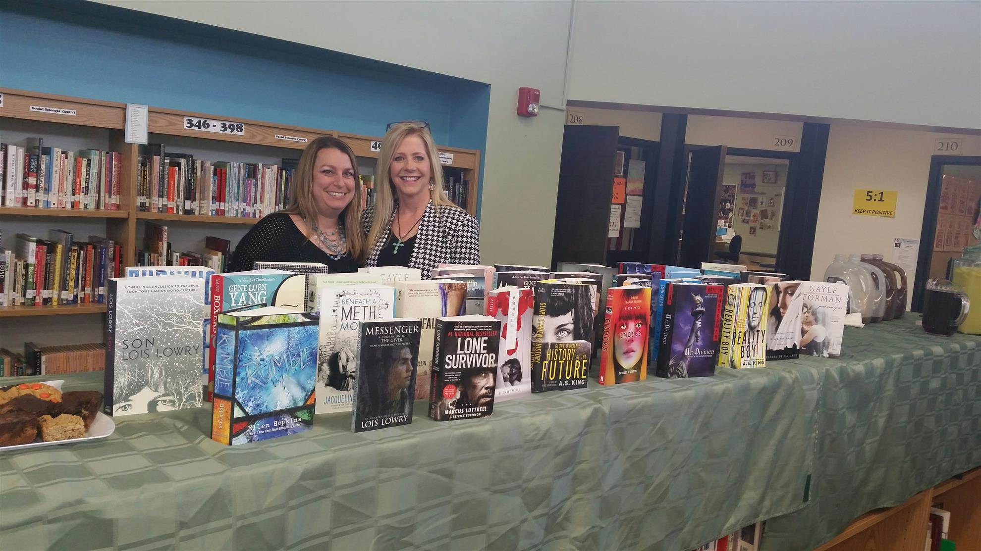 Sandi and Cristiane pictured in front of 2015 Metro High School book donation.
