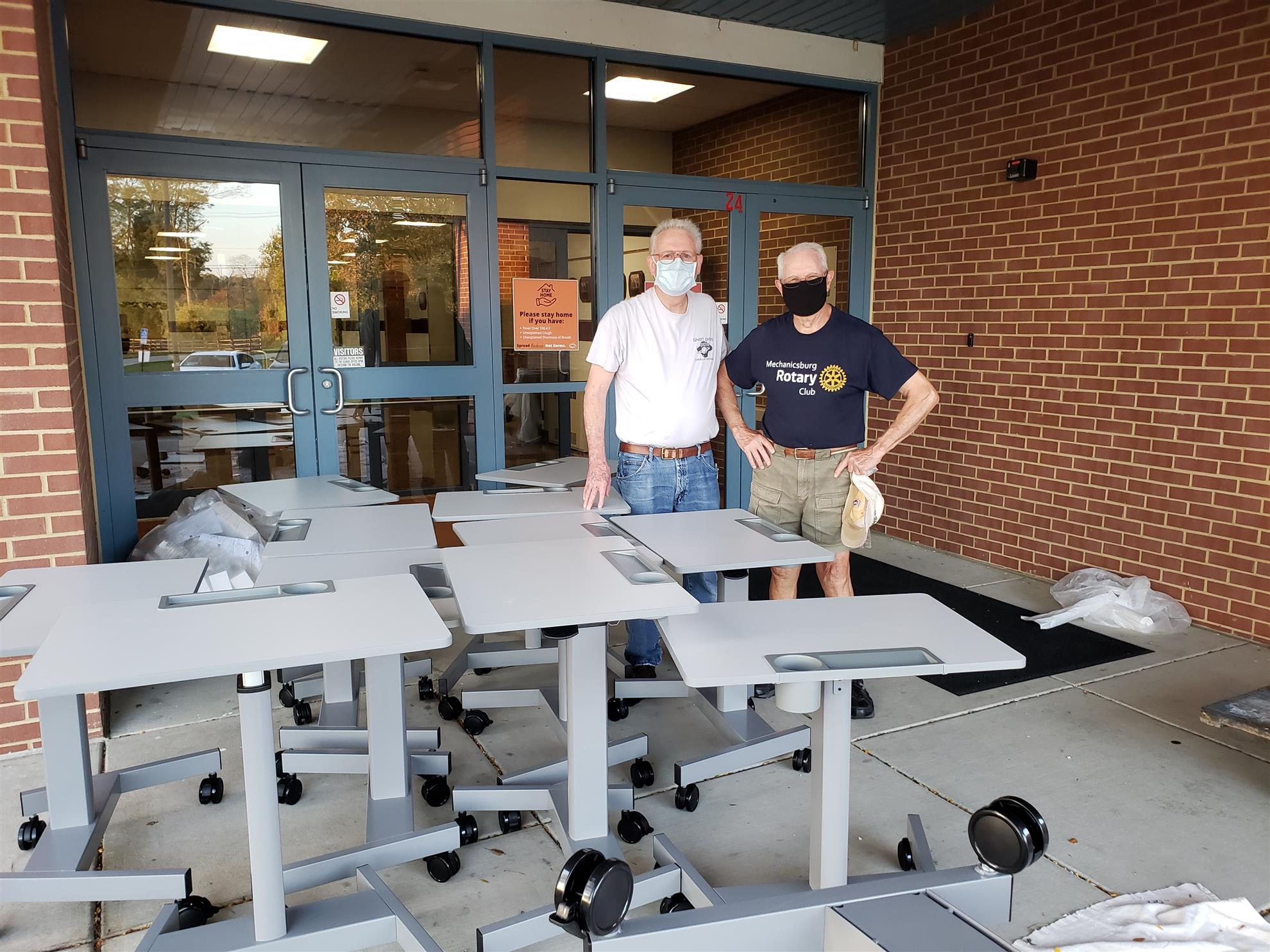 Rotarians Tom Burson & Dave Burns helping to assembly Sit/Stand desks