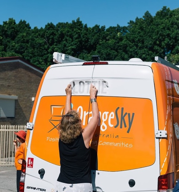 A woman reaching up to add a name sticker to a van. Blue sky, green trees.