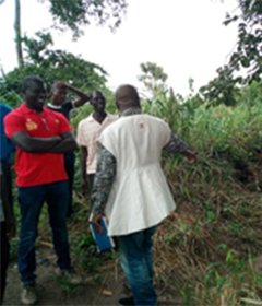 Albert Essien, left, visits the stream that is a source of water for the village.