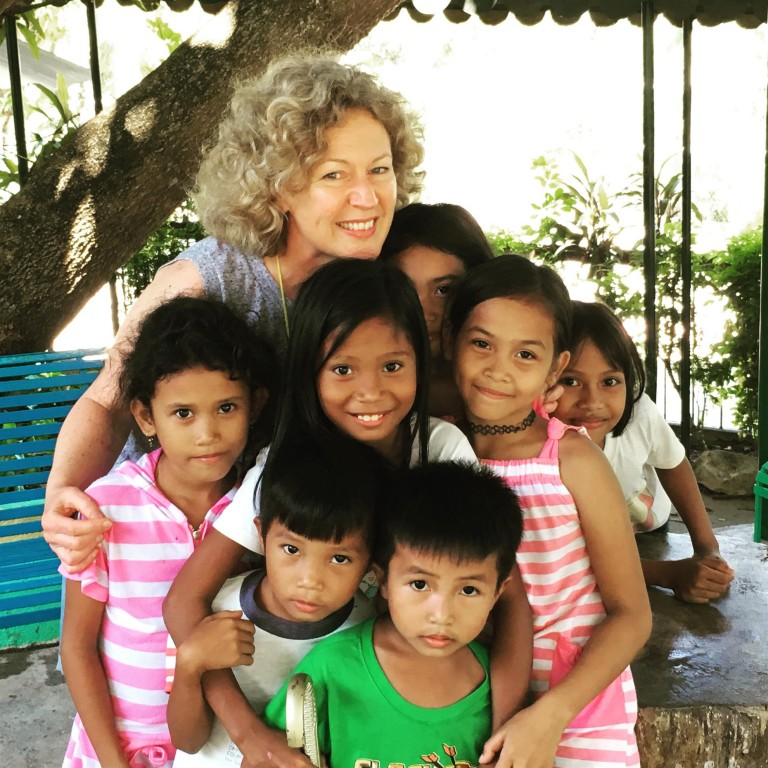 Cathie Macmillan with Filipino children, after checking their ears.