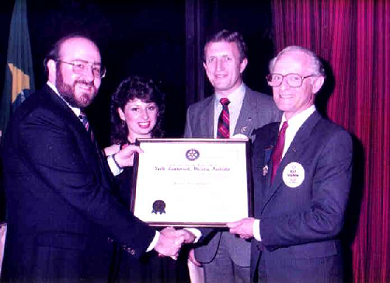 Frank Libman and his wife Fay accepting the Charter from DG Ray Salmon, with Peter Blundell.