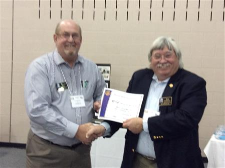 Sam Scroggins, District Public Image Chair, presents 1st Quarter Bulletin Contest Winner a Certificate of Accomplish to Texarkana Sunrise Rotary Club Bulletin Editor Ralph Waits.   The club will receive 200 recognition points for winning the award.