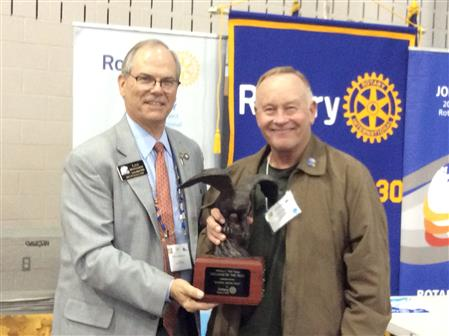 IPDG Lee Montgomery presents Hershel LyBrand with the Rotarian of the Year Award.